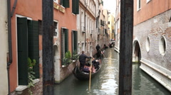 Gondolas along narrow canal in Venice looking through bridge rails - stock footage