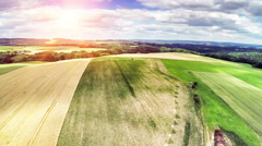 Take off and aerial view of summer countryside with agricultural fields Stock Footage
