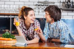Smiling couple smiling and using table together on kitchen - stock photo