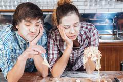 Sad bored couple with flour on faces kneading dough Stock Photos