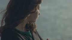 Wind waves hair of gentle girl standing on a cliff Stock Footage