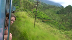 Passenger looking out of window on train journey through tea estates, Kandy Stock Footage