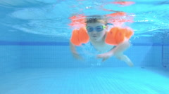 Child swims in the pool. Family travel. Slow motion - stock footage