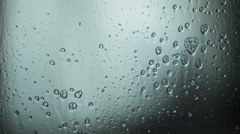 Drops of  spray liquid  flow down on glass. Hand wipes drops. Cold tone Stock Footage