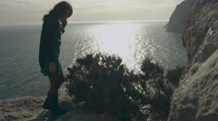Free girl in the dress standing on the cliff and looking at the sea Stock Footage