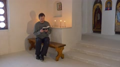 Christmas in Svyatogorsk Monastery Man is Reading the Bible in the Light of Stock Footage