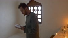 A Man Prays in a Cave Lit by Candles Reading Absorbedly Holding Book Tourist in Stock Footage