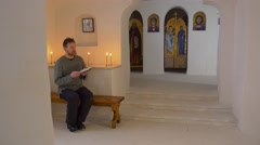 Christmas in Svyatogorsk Man Reads the Bible Sitting on a Bench in the Cave Stock Footage