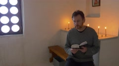 The Bearded Man Sits on a Bench in the Cave Church Tourist Reads a Bible in Stock Footage
