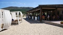 Cala Mesquida Mallorca Majorca: Sun umbrelas and promenade busy Stock Footage