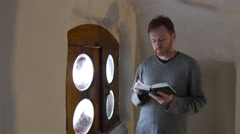 Man With Bible in the Small Room in Monastery Worshiper is Reading Attentively Stock Footage