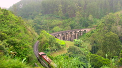 Train winding along the hillside & over bridge, Central Highlands, Sri Lanka Stock Footage
