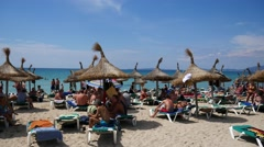 El Arenal Mallorca Majorca: Tourists under straw umbrellas on the beach Stock Footage