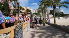 Magaluf Mallorca Majorca: Busy beach bar with people drinking and promenade Stock Footage