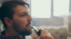 Young stylish man with electronic cigarette vaping Stock Footage