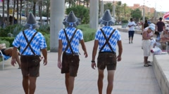 Playa de Palma Mallorca Majorca: 3 guys in tiroller outfit promotion Stock Footage
