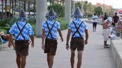 Playa de Palma Mallorca Majorca: 3 guys in tiroller outfit promotion - stock footage