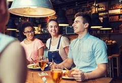 happy friends eating and drinking at bar or pub - stock photo