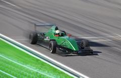 Formula 2 race car racing on a track with motion blur - stock photo