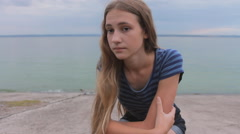 Alone beach girl sea sad. Teen girl lonely and sadness sitting on beach Stock Footage