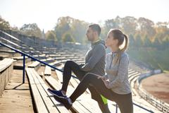 Couple stretching leg on stands of stadium Kuvituskuvat