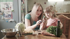 Mother peeling carrot with daughter Stock Footage