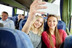 Women taking selfie by smartphone in travel bus Stock Photos