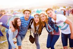 Group of teenagers at summer music festival, sunny day Stock Photos