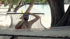 Young man talking on cellphone on hammock on beach, super slow motion 120fps Stock Footage