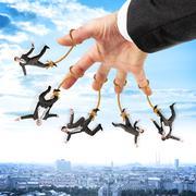 Businessmen hanging on strings like marionette Stock Photos