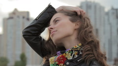 Close up portrait of young woman with hand in hair relaxing in city Stock Footage