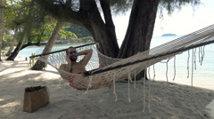 Young man talking on cellphone while lying on hammock on beach Stock Footage