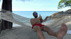 Young man relaxing and drinking beer on hammock on beach - stock footage