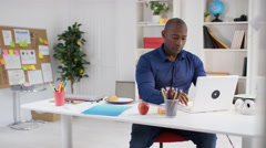 4K Portrait smiling casual businessman working at his desk in modern office Stock Footage