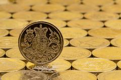 British pound coin on a background of more money. Stock Photos