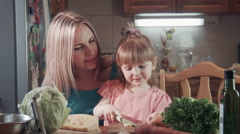 Girl cutting cheese and feeding her mother - stock footage