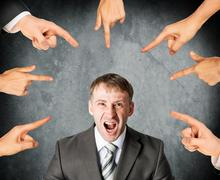 Fingers pointing at screaming stressed businessman - stock photo