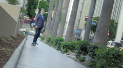 Business man riding on skateboard in Downtown LA HD Stock Footage