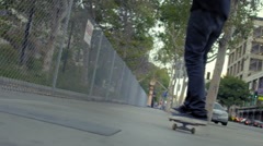 Young mixed race man travels away on skateboard in real time HD - stock footage