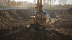 Excavator standing in the middle of a construction site Stock Footage