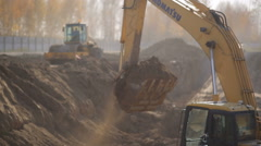 Excavator loading sand into a truck Stock Footage