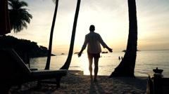 Young man admire and enjoying sunset view on beach - stock footage
