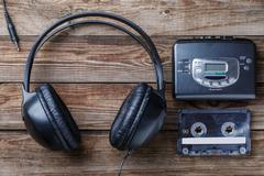 Headphones, player and retro compact cassette over wooden background. Top view - stock photo