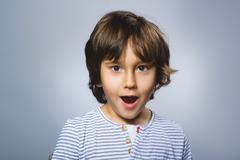 Closeup Portrait of happy boy going surprise on gray background Stock Photos