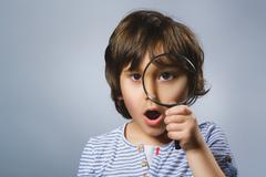 Child See Through Magnifying Glass, Kid Eye Looking with Magnifier Lens over - stock photo