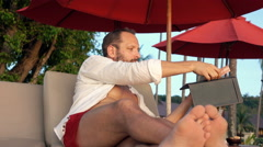 Young man getting change from waiter lying on sunbed in resort  Stock Footage