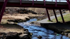 ICELAND, a small lake running under bridge. walkpath. Stock Footage