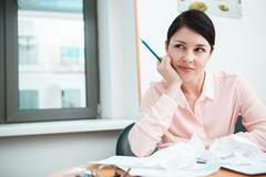 Businesswoman sitting at desk in the office in thoughts Stock Photos