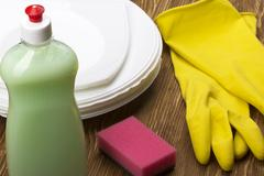 Detergent,sponge, dishes and latex gloves Stock Photos