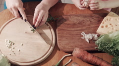 Mother and daughter cutting onion and garlic on wooden board Stock Footage